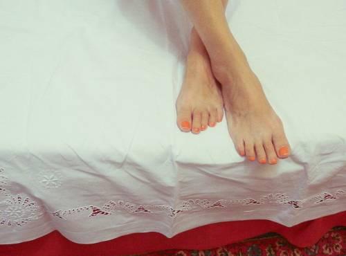 Беспокойные ноги девушки на краю кровати