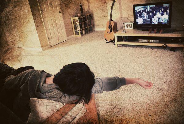 Девушка заснула на диване перед включенным телевизором