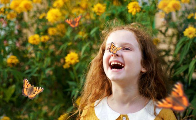 Кудрявая рыжеволосая девочка с бабочкой на носу