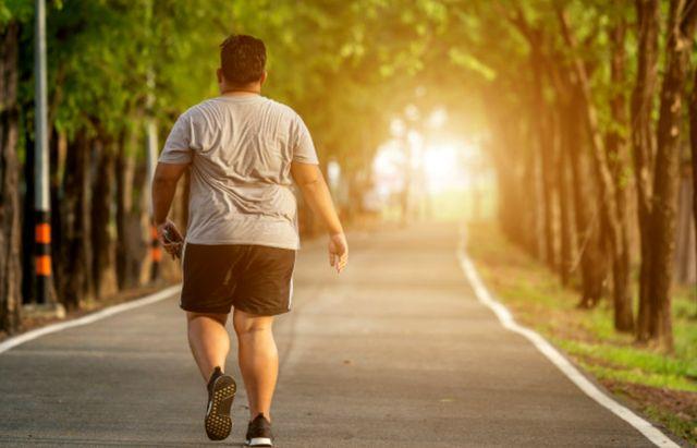 Человек 40 лет с ожирением бежит по парку