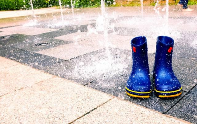 Прохладный поток воды выходит из фонтана, на тротуаре стоят синие детские резиновые сапоги