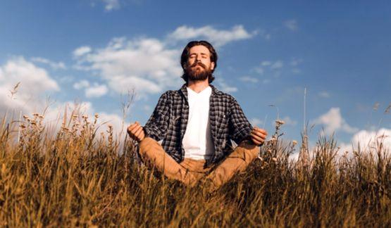 Бородатый мужчина сидит посреди луга и медитирует