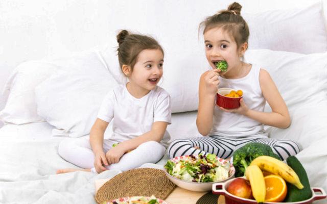 Две девочки обедают полезными фруктами и овощами