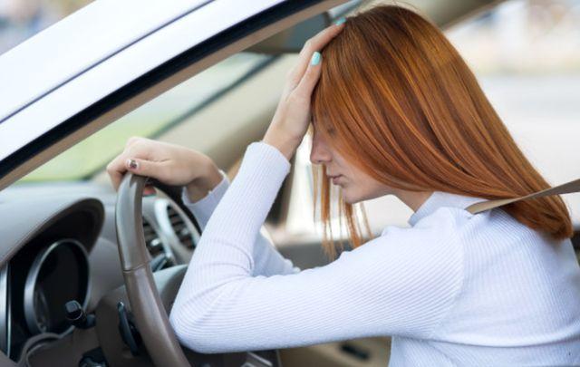 Грустная девушка за рулём автомобиля в дорожном заторе