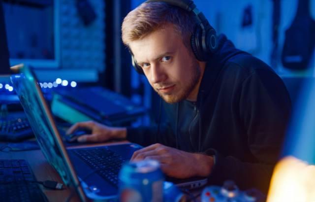 Мужчина с игровой зависимостью склонился над ноутбуком