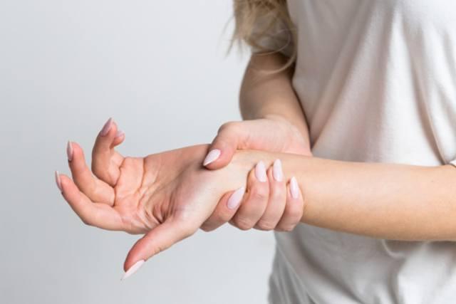 Женщина обхватила руку при покалывании