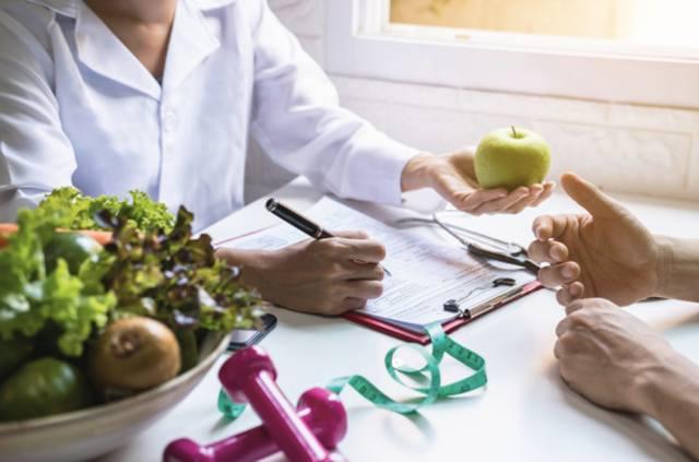 Диетолог дает консультации пациенту со здоровыми фруктами и овощами