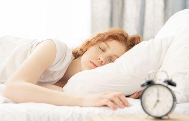 Девушка крепко спит на белой кровати освещённой лучами солнца