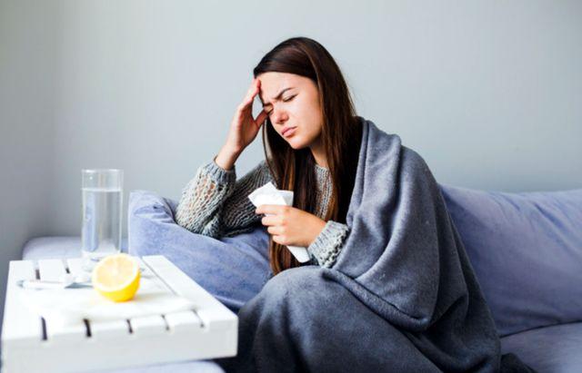 Девушка с головной болью принимает лекарства и запивает лимонной водой
