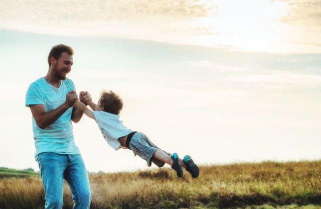Мужчина средних лет играет с сыном на лугу на фоне заходящего солнца