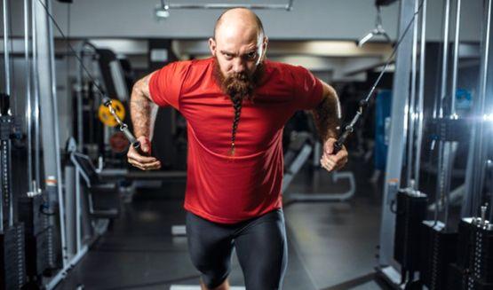 Лысеющий мужчина с бородой тренирует мышцы на спортивном тренажёре