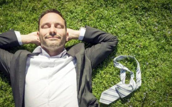 Мужчина за 40 лежит на траве и наслаждается жизнью