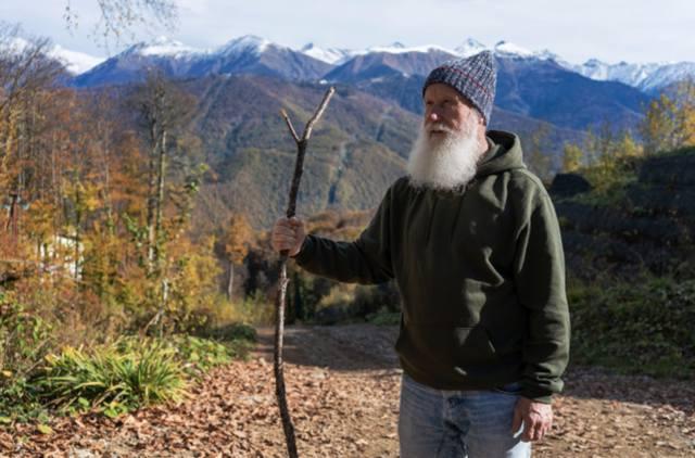 Пожилой мужчина с седой бородой и посохом в руке идёт по дороге на фоне горных вершин