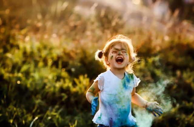 Очаровательная девочка измазала одежду краской и радуется