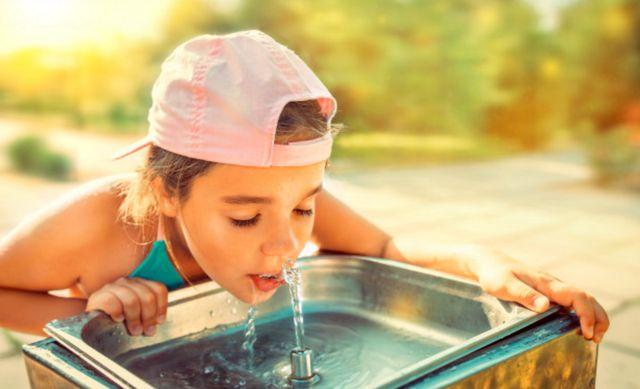 Загорелая девочка в кепке пьёт воду из фонтанчика
