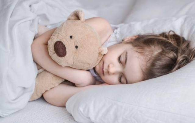 Девочка крепко спит в кровати обняв мягкую игрушку
