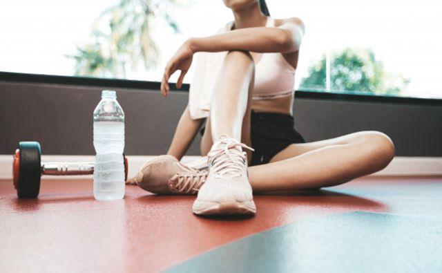 Девушка отдыхает после тренировки рядом с бутылкой воды и гантелей