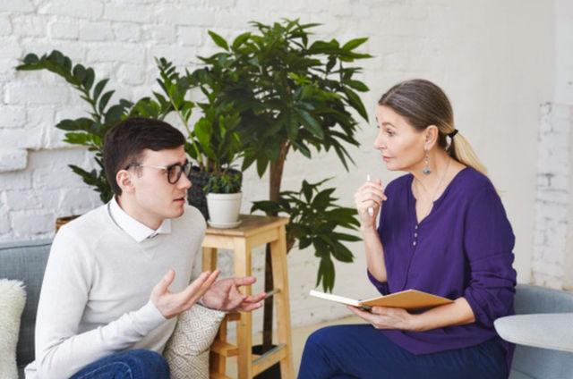 Молодой мужчина в очках на приёме у психотерапевта