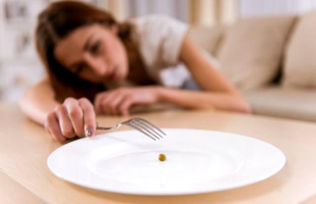 Измученная от недоедания девушка лежит на диване