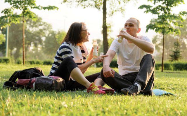 Счастливая зрелая пара 40 лет сидит в парке и пьёт йогурт