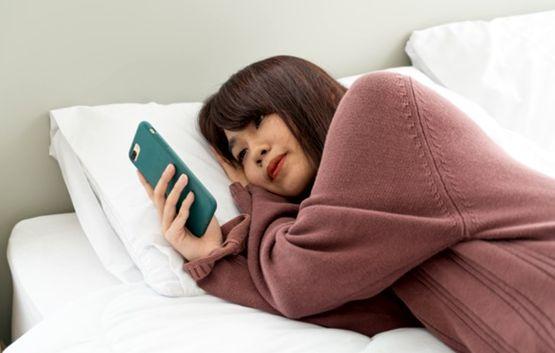 Девушка лежит на боку и смотрит на экран смартфона