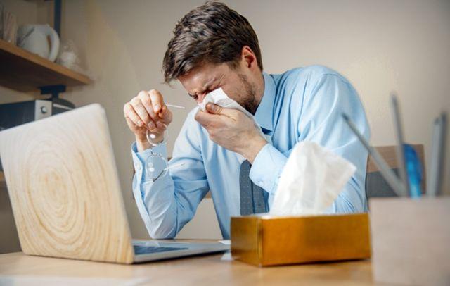 Мужчина за ноутбуком страдает от насморка
