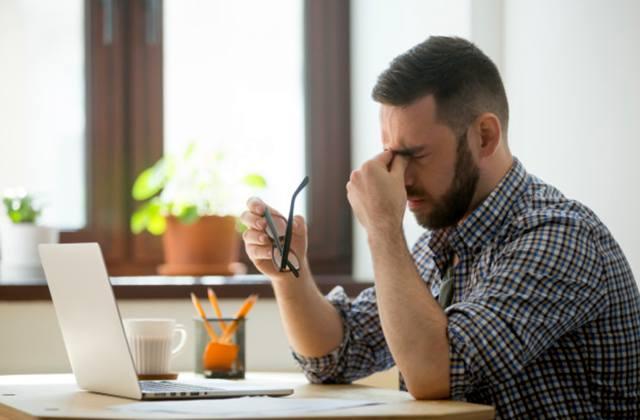Сонливый мужчина на рабочем месте делает массаж переносицы