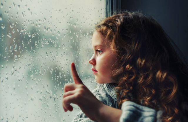 Унылая маленькая девочка смотрит в окно на падение капель дождя