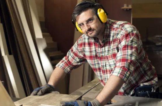 Мужчина среднего возраста работает в столярной мастерской