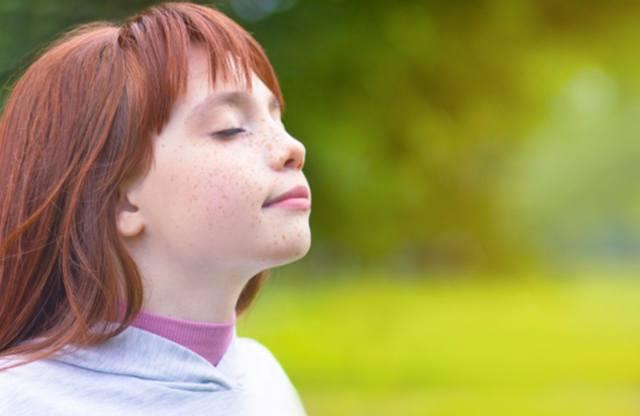 Девочка с рыжими волосами делает глубокий вдох