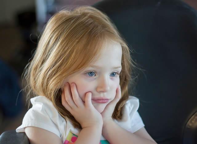 Увлеченный взгляд девочки, смотрящий телепередачу