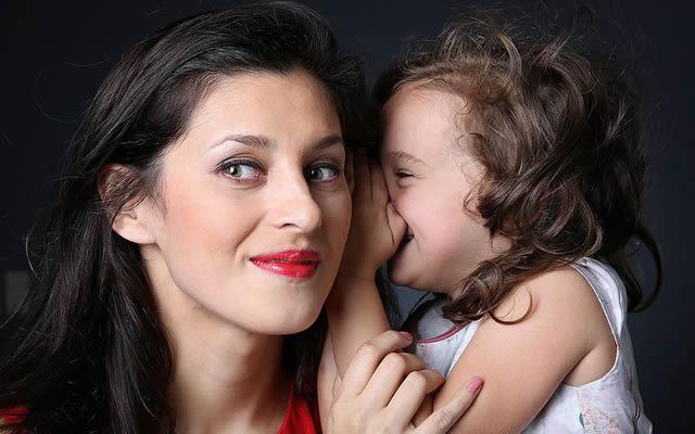 Девочка шепчет маме секрет на ушко