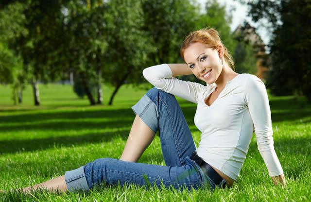 Красивая девушка сидит на траве в летнем саду