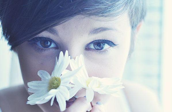 Счастливая девушка нюхает ромашки