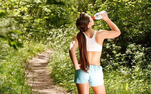 Девушка пьёт чистую воду во время пробежки по парку
