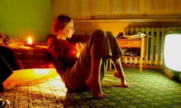 Сидящая на полу девушка за просмотром телепередачи
