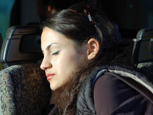 Девушка, спящая в кресле автобуса