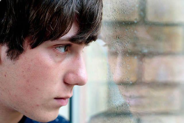 Парень с грустным взглядом смотрит в окно на дождь