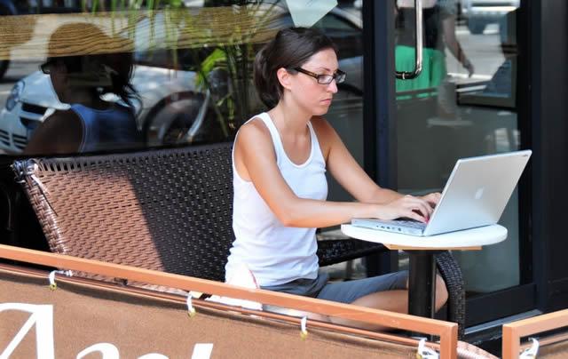 Девушка в кафе работает на ноутбуке