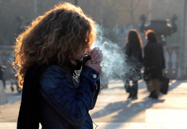 Девушка, прикуривающая сигарету на улице