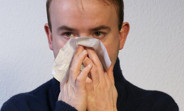 Мужчина высмаркивается в одноразовый носовой платок