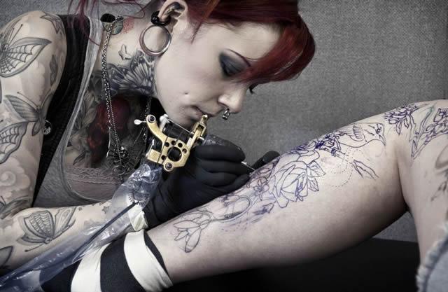Девушка набивает татуировку на ноге