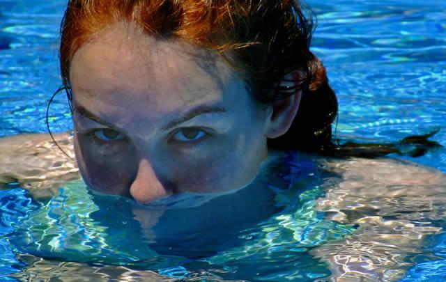 Девушка купается в бассейне