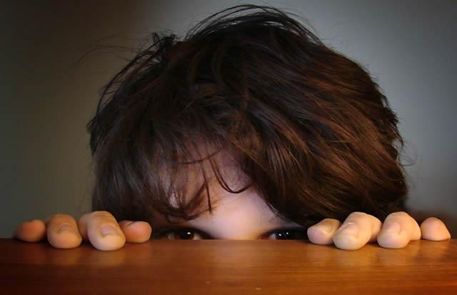 Напуганный ребенок прячется за столом