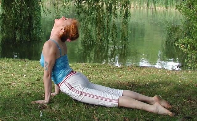 Девушка выполняет позу кобры на берегу реки