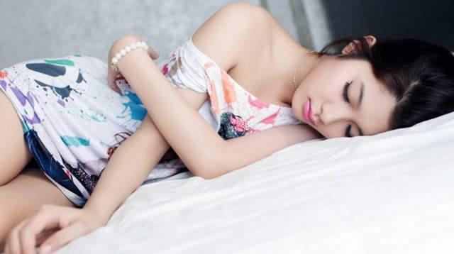 Красивая японская девушка спит на левом боку
