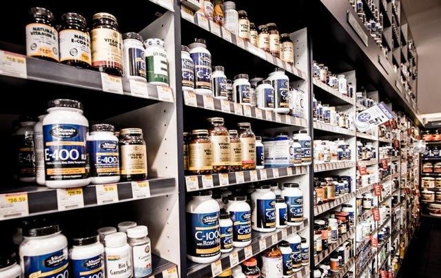 Полки аптеки, заставленные баночками с витаминными добавками