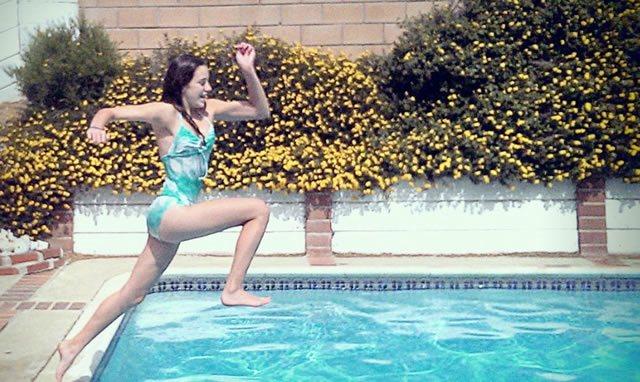 Девушка с разбегу прыгает в бассейн