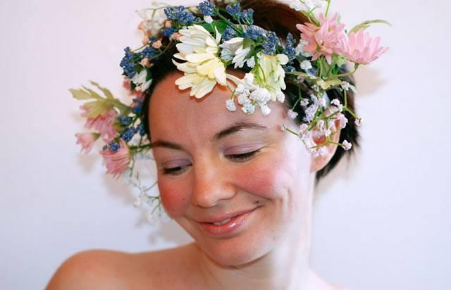 Девушка с ало-белым цветочным венком на голове