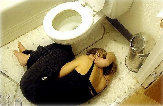 Девушка с тошнотой лежит на полу около унитаза